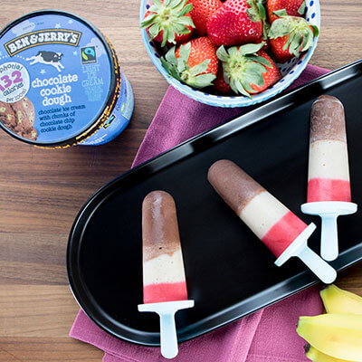 Smoothie Pops on a plate with a pint of Moophoria Chocolate Cookie Dough and a bowl of strawberries